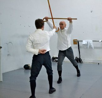 Cane fencer (facing) executes double handed parry of blow to the head by adversary.